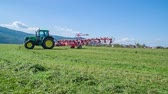 грабли : Agricultural machinery is moving fast. A tractor is driving across the field.