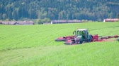 ancinho : Farmers are getting on fields because they need to cut grass with agricultural machinery. The day is beautiful and sunny. Stock Footage