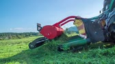 грабли : A beautiful green grass is flying around when the farmers are cutting it with the machinery. The day is sunny and warm.