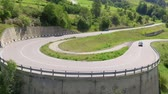 demônio : A big sharp curve. A car is driving uphill into a curve. The landscape is green during this time of year.
