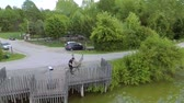 виноградник : A young man sits down on his bicycle and drives away. He is going to drive along the river. Стоковые видеозаписи