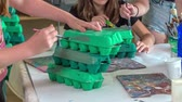предметы : A few school children are colouring egg cartons green. they are having fun in their art class. Стоковые видеозаписи
