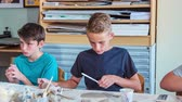 предметы : Boys are having fun making something from clay in their art class.
