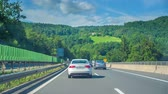 tavuskuşu : A car is driving on a fast line after another car. Its a nice sunny day in Slovenia.