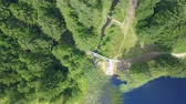 trilhas : There is a path next to a dark blue lake and it is leading parallel to the lake in the forest. Aerial shot. Stock Footage