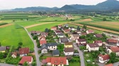 serio : We can see a beautiful green nature and the village in the front. Aerial shot. Slovenia is a really gorgeous country.