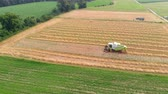 szlovénia : A combine is harvesting wheat on a hot summer day. Aerial shot. Its a really nice day. Stock mozgókép