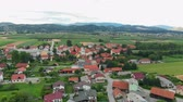 szlovénia : Very nice green fields behind a village. Aerial shot. Slovenia is very beautiful and green. Stock mozgókép