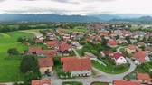szlovénia : Amazing green meadows on one side of the village. Aerial shot. The roofs are red.