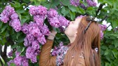 Pretty girl is enjoying the scent of lilac. Breathes the fragrance of flowers Стоковые видеозаписи
