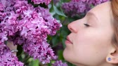 cheirando : Pretty girl is enjoying the scent of lilac. Ð¡lose up