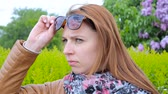 Dissatisfied girl looks at people. Woman on the park with sunglasses