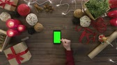christmass : Top view using smartphone scroll top and tap at wooden desk from above with christmass decoration