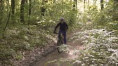 bike ride : Young sports man riding bicycle on the tree forest road, sunny spring day, 120FPS slowmotion Stock Footage