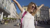 Beautiful caucasian tourist girl in fashionable sunglasses and pink headphones is enjoying her sightseeing tour time in the old city center while wind blowing, sunny day, slow motion