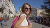Attractive caucasian tourist girl in stylish sunglasses and pink headphones is looking around while walking cheerfully in the old city center, sunny day, slow motion Stok Video