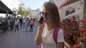 Beautiful smiling caucasian tourist girl in stylish sunglasses is talking on the phone happily in the old city center, sunny day, slow motion Stok Video