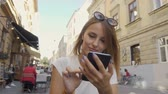 Pretty smiling fair hair tourist girl with stylish sunglasses on her head is texting a message on her smartphone happily in the old city street, sunny day, slow motion