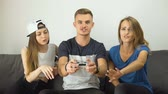 botão de pressão : Gripped caucasian teens playing a video game on the comfortable sofa, slow motion Vídeos