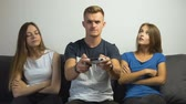 botão de pressão : Cute caucasian teen girls tired of gripped teen boy playing a video game on the comfortabe sofa, slow motion