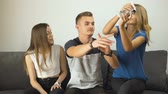 botão de pressão : Lovely caucasian teen girls take away a gamepad from gripped teen boy playing a video game on the comfortabe sofa, having fun, slow motion