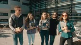 quatro pessoas : Group of young attractive students walk before modern building, have a pleasant talk, cafe sunny day steady 120FPS slowmotion