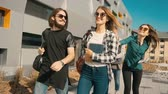 collaborating : Casual style group of students walk along university modern building, have a pleasant talk, sunny day steady 120FPS slowmotion