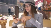 szerény : Smiling girl, in grey striped hat and shirt, texting on mobile phone during coffee time in outdoor cafe, slowmotion