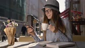 szerény : Smiling girl, in grey striped hat and shirt, using mobile phone and enjoys cup of coffee in outdoor cafe, slowmotion
