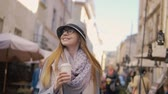 скромный : Relaxed caucasian girl, in striped hat and glasses, holding coffee while walking in the street, sunny day, slowmotion