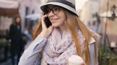 szerény : Smiling caucasian girl, in striped hat and coloured scarf, making a phone call while walking in the street, sunny day, slowmotion
