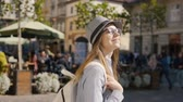 скромный : Intelligent caucasian girl, with rucksack, walking happily in historical city center, sunny day, slowmotion Стоковые видеозаписи