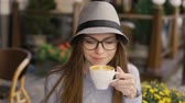 pausa pranzo : Smiling caucasian girl, in a grey striped hat and glasses, having morning latte in a cafe, outdoor slowmotion