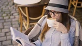 скромный : Beautiful caucasian girl, in a grey striped hat and glasses, enjoys latte coffee while reading in the outdoor cafe, slowmotion