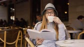 szerény : Beautiful caucasian girl, in a grey striped hat and glasses, reading a book during coffee time in the outdoor cafe, slowmotion Stock mozgókép