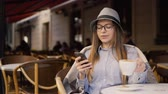 скромный : Smiling girl, in a grey striped hat and glasses, using mobile phone during coffee time in the outside cafe, slowmotion