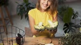 brokolice : Smiling girl showing fresh broccoli at the wooden table full of healthy nutritious food