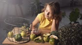 brokolice : Beautiful, slim girl having smooze at the wooden table full of green vegetables and fruits