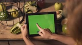 栄養 : Girl using a tablet with a green display at the kitchen table with green vegetables and fruits, touch and slide gestures
