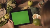 栄養 : Woman using a green screen tablet at the table full of fresh green vegetales and fruits, touch and slide gestures