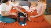 vesta : Two smiling friends packing traveling bag while preparing for a trip, indoor shot on large red bed