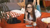 jegy : Beautiful long-haired girl in glasses chatting on the phone about upcoming trip, indoor shot in cozy bedroom