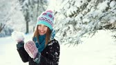 śnieżka : Young happy girl playing snowballs in the winter park, outdoor sunny day slowmotion