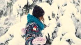 śnieżka : Young happy girl wears holiday sweater playing with snow in the winter park, outdoor sunny day slowmotion
