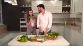 mikrovlnná trouba : Beautiful couple having fun as cooking, handsome bearded man slicing cucumber, pretty dark-haired woman singing with broccoli in hand, concept of happy family life and healthy food