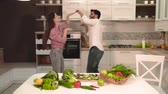 brokolice : Happy family couple dancing in the light spacious kitchen, indoor shot behind the table full of fresh, nutritious vegetables and fruit