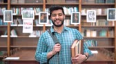enciclopédia : Portrait of handsome intelligent student in the library, bearded asian man walking happily, holding books and black backpack, wearing blue checked shirt and jeans