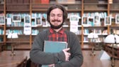 enciclopédia : Young bearded man holding books, standing joyfully in library, wearing checked shirt and gray sweater, indoor portrait shot