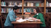 ansiklopedi : Two lovely students working in pair, talking about read material with pleasure, good-looking bearded boy and beautiful brunette sitting at square library table next to the bookshelves Stok Video
