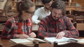 кампус : Two happy friends reading in large light library, smart bearded boy looking through the pages, bright girl in glasses talking to the mate, wearing stylish checked shirts